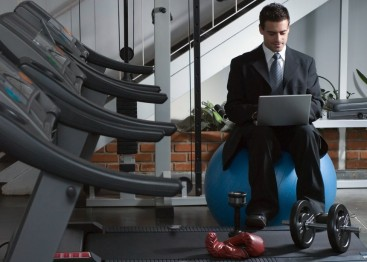 man-in-business-suit-sitting-in-a-gym-on-his-laptop